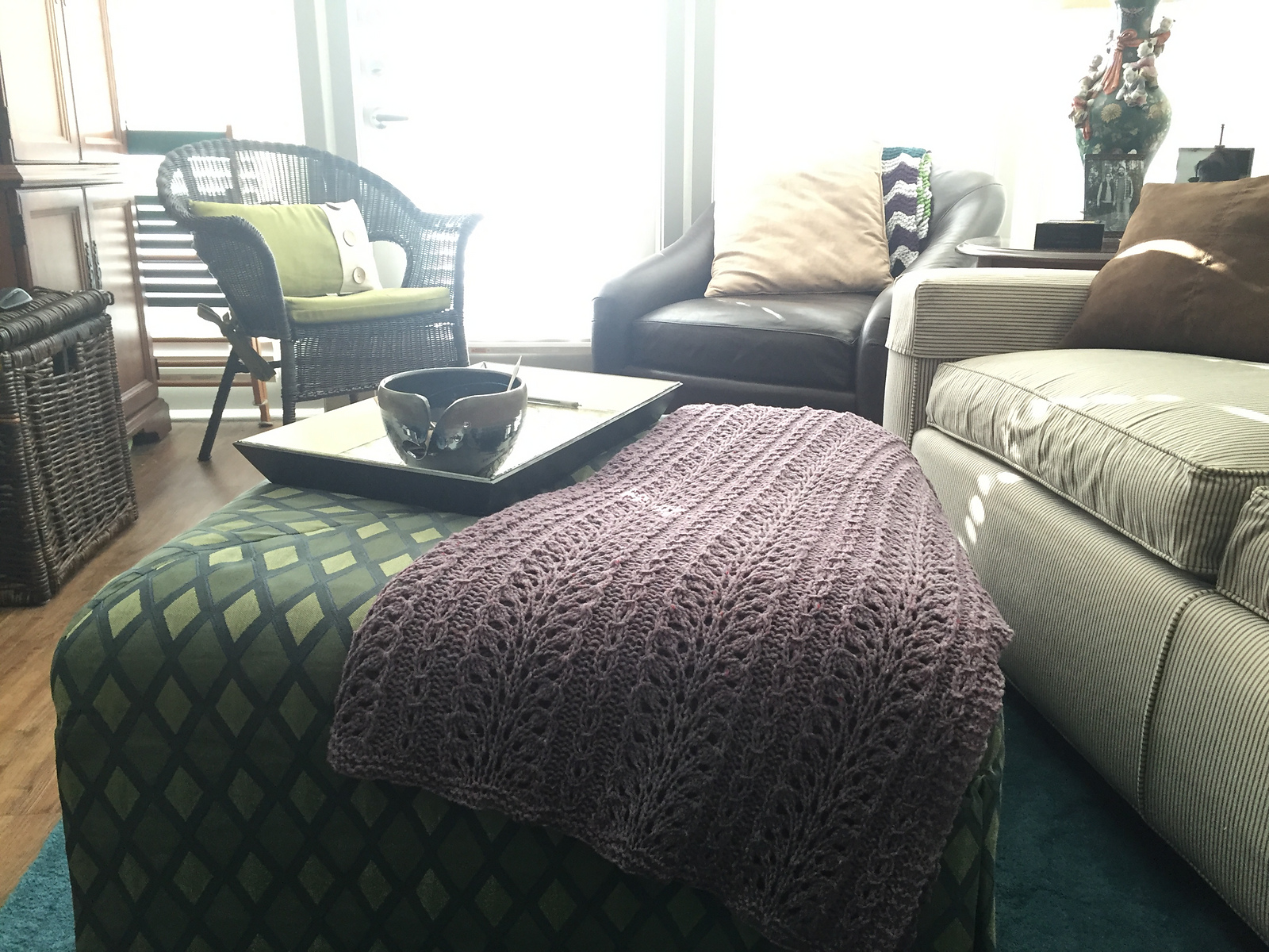 hand knit blanket laid over an ottoman